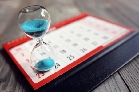 Hour glass on calendar concept for time slipping away for import